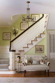 ... ensure this traditional foyer is anything but boring. A lovely beige  settee offers sophisticated seating, and a classic wood staircase leads  upstairs.