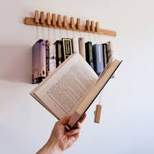 Each book is held by adjustable small wooden plates that can accommodate  different sizes of books and keeps the pages intact.