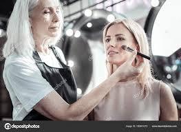 serious makeup artist doing her job stock photo