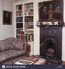 oil painting above small cast iron fireplace i a nineties living room with built in bookcase and a patterned sofa