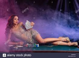 Girl in golden dress playing poker at casino, holding money, laying on  table with chips, cards on it. Black, smoke background. Gambling. Close-up  Stock Photo - Alamy