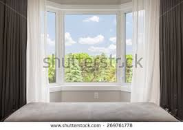 bay window with drapes curtains and view of trees under summer sky bay drapes w61