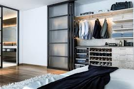 small bedroom closet for men with a sliding door and light finished cabinetry and shelving