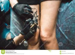 Tattoo Male Artist Makes A Tattoo On A Female Leg Stock Image