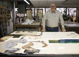 david haight stands at a large light table where components of a cur project are laid out always an aficionado of stained glass he still has some of