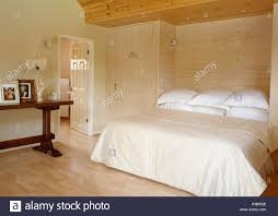 Light Wood And White Bedroom Light Wood Panelled Wall Behind Bed With White Pillows And