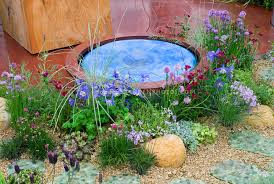 Small Picture Tiny water feature in garden of flowers Plant Flower Stock