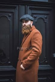 portrait of stylish bearded man posing over black door stock photo