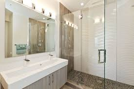 these wavy tiles along with the pebble like shower floor and the wood details give this bathroom a modern beachy look