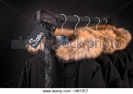 Coat Rack Black Friday A lot of black coats jacket with fur on hood hanging on clothes 74