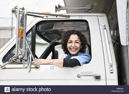 Hispanic Woman Truck Driver And Company Delivery Truck Stock Photo