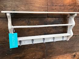 a beautiful grey washed wooden wall shelf with hooks