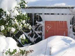 detail of front door of house blocked by pile of snow after snowstorm stock photo