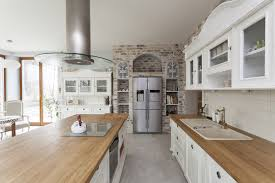 white kitchen with wood counters and brick accent wall