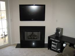 black marble fireplace with heart under wall mounted f flat tv on white painted home