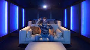theater room lighting. Man Wathing A Movie Theater Room Lighting
