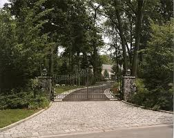 Driveway Entrance with Custom Iron Gates, Stone Piers and Cobblestone Inlay  traditional-landscape