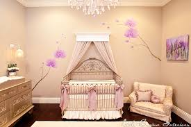 gorgeous nursery with silver iron crib dressed in lavender silk and ivory crib bedding with a pale lavender canopy flanked by a purple orchid wall mural