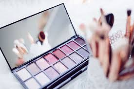 photo of eyeshadow palette and container of makeup brushes
