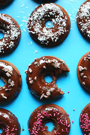 glazed chocolate donuts topped with sprinkles cacao nibs or shredded coconut for a vegan