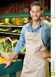 handsome young s clerk standing near stall in supermarket handsome young s clerk standing near stall in supermarket