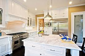 Luxury galley kitchen with white cabinets marble counters and mocha oak  hardwood floors