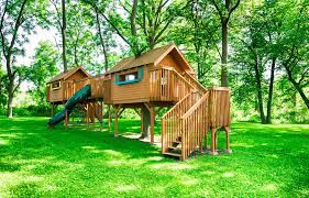 incredible playhouse structure that is two playhouses connected by bridge and includes a slide