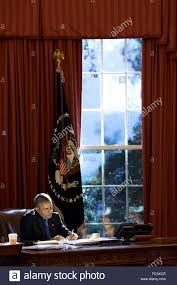 obama oval office desk. U.S President Barack Obama Works At The Resolute Desk As Afternoon Light Streams Through Window In Oval Office Of White House October 23,