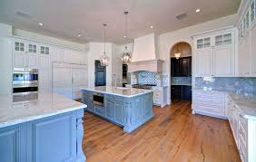 Luxury kitchen with blue and white main cabinets, painted blue island and  marble counters