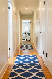 neutral transitional hallway with blue patterned rugs
