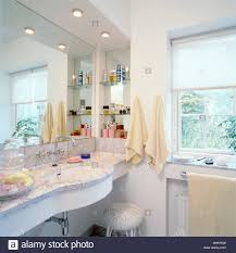 stock photo under set basin in marble vanity unit below mirror and recessed lighting in small white bathroom with white blind on window