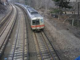 a new haven line train of m2 m4 m6s makes its way along the woods near the bronx river north of the botanical garden station