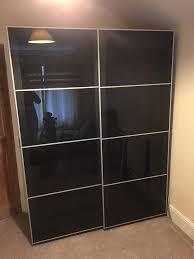 ikea pax wardrobe with black glass sliding doors