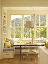 A comfortable breakfast nook with a stained wooden kitchen table, a storage  bench with seat