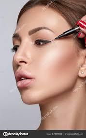 woman doing eye make up using black eye liner beautiful woman portrait beauty skin healthy and perfect makeup photo by ovcharenkoviktoria