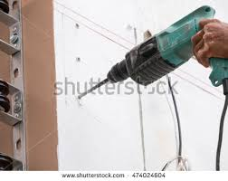 hand drilling machine. worker drilling the wall with drill machine in hand