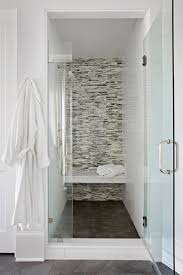 luxurious walk in shower design with linear mosaic glass tile shower surround and floating shower bench over dark gray shower floor