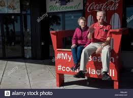 senior couple enjoys big chair on the boardwalk at myrtle beach south carolina usa stock