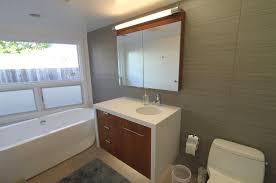 victorian style round mirror with thick frame plain white ceramic bathtub white wooden wall mounted shelf