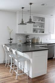 wall mount cabint with shelves and haning lamps over black granite kitchen countertop also 3 vintage interesting white kitchen counter stools with backs