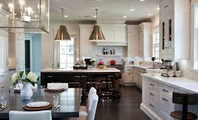 two tone kitchen features visual comfort lighting goodman hanging lamps in hand rubbed antique brass over brown kitchen island topped with white marble