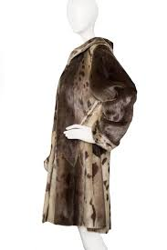 a 90s yves saint lau seal skin coat with a cross closure and