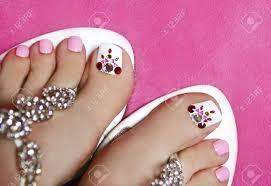 ラインス トーンのピンクと白の色で S 足の女性にペディキュアします