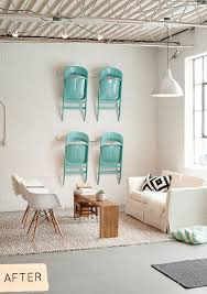 brightly colored folding chairs hang from the wall for additional seating studio or office