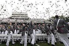 college admissions in the united states  outdoors men in gray uniforms throwing hats in the air