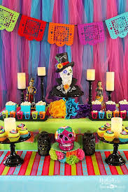use a a large sugar skull decoration or a vase filled with oversized tissue paper flowers as a centerpiece add prayer candles as accents and hang papel