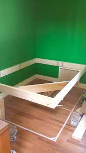 First, he put three sets of deck screws into his frame every 32 inches.  Then he attached it to the two sides of his wall. Putting tape on the  ground let him ...