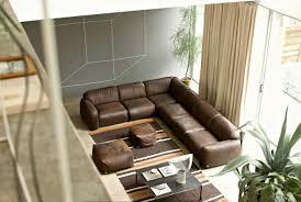 area rug for living room mixed with dark brown l shaped leather sofa and small ottoman also light grey wallpaper in cubic motif