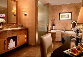 trumph hotel suite room wooden bathroom vanity brown marble wall and floor classic wall lamp 2 candle holder exclusive bathtub shower glass door modern
