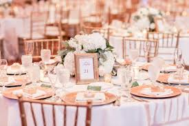 wedding reception decor round table with white tablecloth gold chiavari chairs gold chargers gold frame with table number low white hydrangeas and